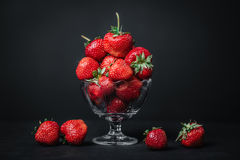 Ripe juicy strawberries in a glass on a dark background. Ripe juicy strawberries in a glass Royalty Free Stock Photos