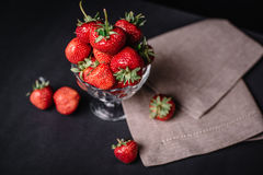 Ripe juicy strawberries in a glass on a dark background. Ripe juicy strawberries in a glass Stock Image
