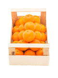 Ripe, juicy tangerines in a wooden box stacked as pyramid Stock Image