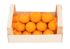 Ripe, juicy tangerines in a wooden box stacked as pyramid Royalty Free Stock Images