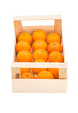 Ripe, juicy tangerines in a wooden box stacked in a one row Royalty Free Stock Photo