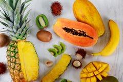 Ripe juicy tropical summer seasonal fruits mango papaya pineapple kiwi bananas wood background lifestyle super foods. Ripe juicy tropical summer seasonal fruits royalty free stock photography
