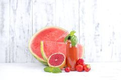 Ripe juicy watermelon, grapefruit, basil. berries and fresh juice in a plastic bottle. Copy space stock photo