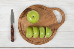 Ripe juicy yellow and green apples lie on wooden board with a knife next to it in top view. stock image