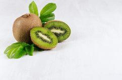 Ripe kiwi with juicy slice and drop juice, green young leaves on white soft wood board. Fresh summer background with fruits. Ripe kiwi with juicy slice and drop royalty free stock photos