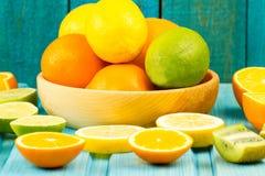 Ripe kiwi, lime, lemon, orange fruit on wooden vintage background. Healthy vegetarian food. Stock Image