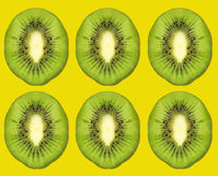 Ripe kiwi slices on yellow background. Stock Photos