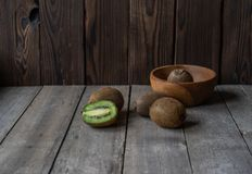 Ripe kiwi on a wooden background in a wooden bowl royalty free stock image