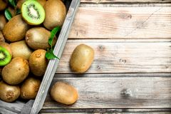 Ripe kiwi in a wooden box. On wooden background stock photo