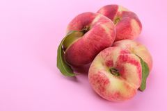 large fig figs peach with a green leaf close-up on a bright paper pink background royalty free stock photography
