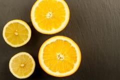 Ripe lemon and orange on a black stone background Royalty Free Stock Photography