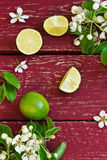 Ripe lime. And branches with flowers on the old wooden background. top view. healthy fruit from his garden Stock Photo