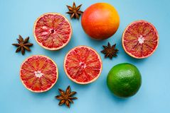 A ripe lime, red oranges and anis stars. On blue paper background stock photography