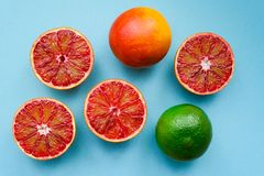 A ripe lime and red oranges. On blue paper background Royalty Free Stock Images