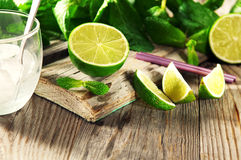 Ripe lime. On a wooden table with mint. Ingredients for cocktail Stock Photo