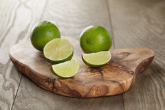 Ripe limes on olive board Royalty Free Stock Images