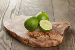 Ripe limes on olive board Stock Photo