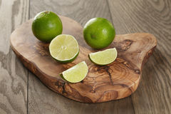 Ripe limes on olive board Royalty Free Stock Photo
