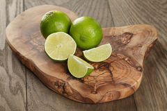 Ripe limes on olive board. Rustic style Stock Photography
