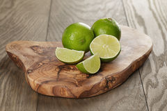 Ripe limes on olive board Royalty Free Stock Image