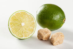 Ripe limes and pieces of unrefined cane sugar Stock Photos