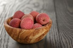 Ripe lychees in wood bowl on table Stock Image