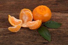 Ripe Mandarin fruit with leaves and one peeled open Stock Photos