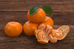 Ripe Mandarin fruit with leaves and one peeled open Stock Images
