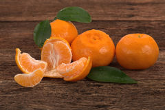 Ripe Mandarin fruits and one peeled open Royalty Free Stock Photos