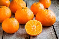 Ripe mandarins cut on a wooden background Stock Photo