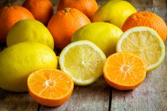 Ripe mandarins and lemons cut into a rustic wooden background Stock Image
