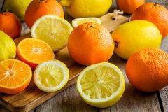 Ripe mandarins and lemons on a cutting board Stock Images