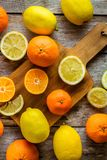 Ripe mandarins and lemons on a cutting board Stock Photos
