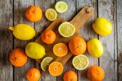 Ripe mandarins and lemons on a cutting board Royalty Free Stock Photos