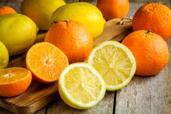 Ripe mandarins and lemons on a cutting board Royalty Free Stock Images