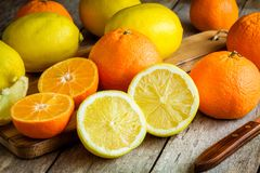 Ripe mandarins and lemons on a cutting board Royalty Free Stock Photography