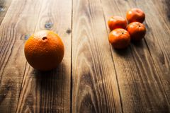 Ripe mandarins and orange on a wooden bacground. A ripe mandarins and orange on a wooden bacground Royalty Free Stock Images