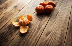 Ripe mandarins and peeled mandarin on a wooden bacground. A ripe mandarins and peeled mandarin on a wooden bacground Stock Image