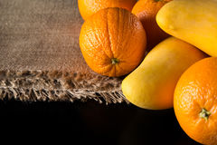 Ripe mango and fresh oranges is great fruits for healthy raw veg. Yellow mango and ripe oranges on the jute tissuie on the black table in the kitchen royalty free stock images