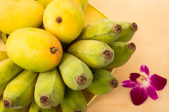 Ripe Mango and Raw Banana on a Wooden Table with Orchid Flower. Ripe Mango and Raw Banana on Wooden Table with Orchid Flower Stock Image