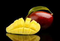 Ripe mango with slice and leaf isolated black background Royalty Free Stock Photos
