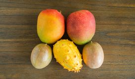 Mangoes, passion fruit and kiwano melon on a wooden table viewed from above royalty free stock photo