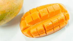 Ripe mangoes in white background/sliced delicious mango to eat. Mangoes are in season March through June. Learn how to tell if a mango is ripe and watch our stock image