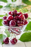 Ripe maroon cherries in a glass vase and a jar. Ripe and fresh burgundy cherries in a glass vase and a jar for healthy food and preparations for the winter Royalty Free Stock Images