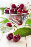 Ripe maroon cherries in a glass vase and a jar. Ripe and fresh burgundy cherries in a glass vase and a jar for healthy food and preparations for the winter Stock Photos