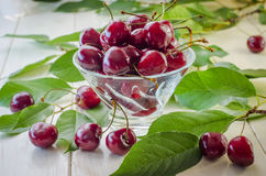 Ripe maroon cherries in a glass vase and a jar Stock Photos