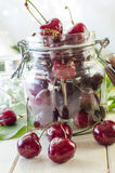 Ripe maroon cherries in a glass vase and a jar. Ripe and fresh burgundy cherries in a glass vase and a jar for healthy food and preparations for the winter Stock Image