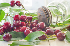 Ripe maroon cherries in a glass vase and a jar Royalty Free Stock Photo