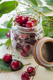 Ripe maroon cherries in a glass vase and a jar Stock Images