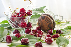 Ripe maroon cherries in a glass vase and a jar. Ripe and fresh burgundy cherries in a glass vase and a jar for healthy food and preparations for the winter Stock Photography